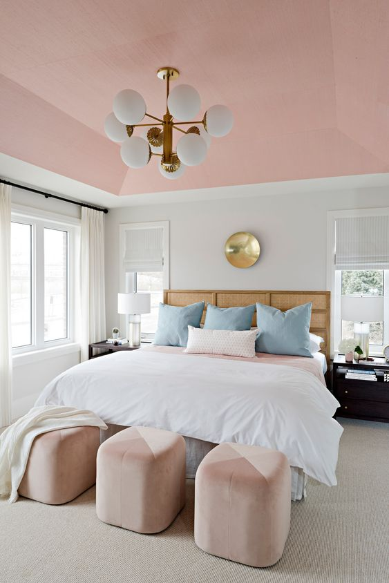 a refined mid-century modern bedroom with a pink ceiling, pink and blush ottomans for softening the color scheme