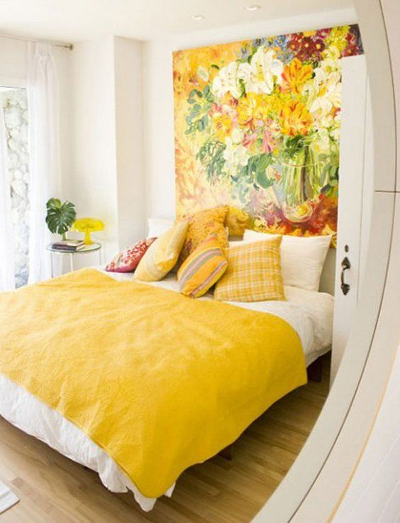 a vivacious bedroom with an oversized floral artwork that takes a whole wall and matching yellow bedding and pillows