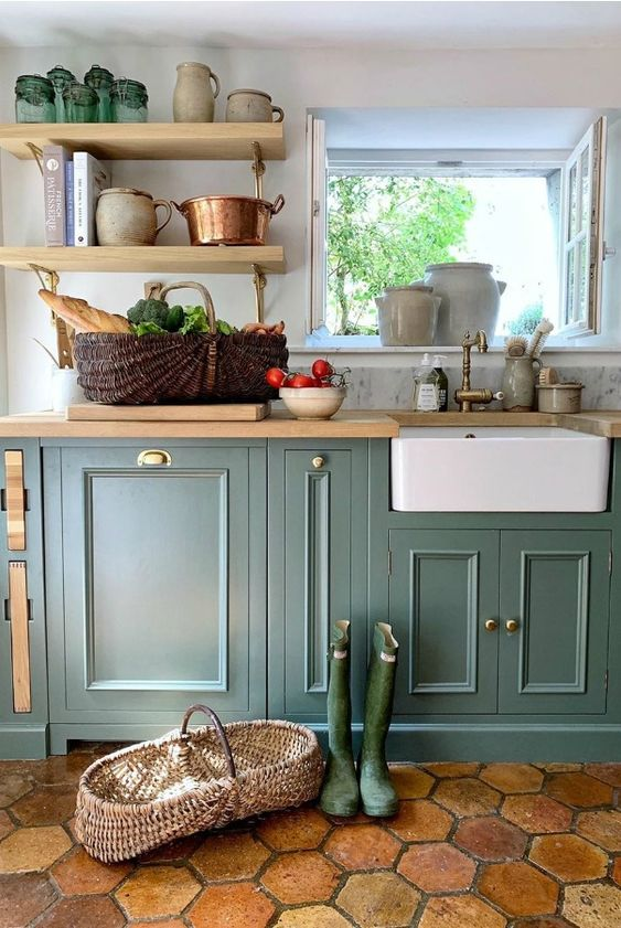 a French farmhouse kitchen with dark green cabinets, butcherblock countertops and matching shelving plus a tiled floor