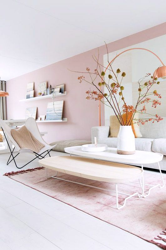 a Scandinavian living room with light pink walls and a matching rug, neutral furniture and ledges with gallery walls