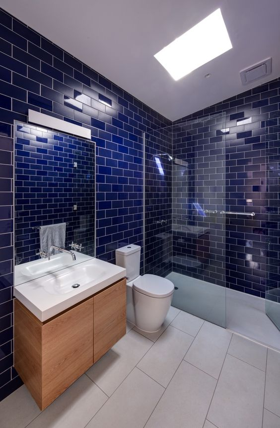 a bathroom clad with deep blue subway tiles, a neutral ceiling and floor and a floating vanity