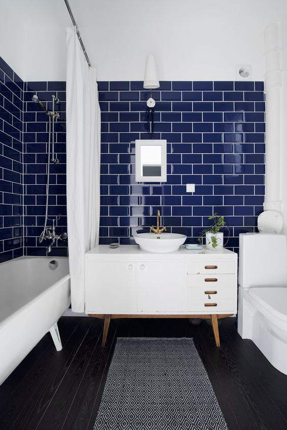 a bathroom with navy subway tiles, a white ceiling and white furniture and appliances for a contrast