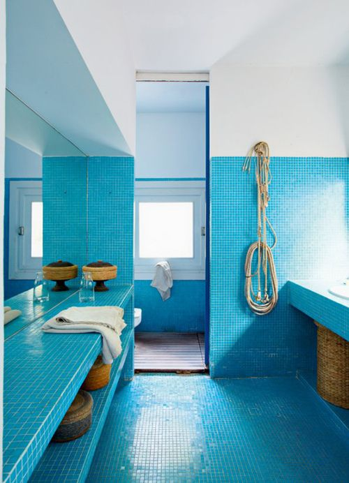 a beach bathroom clad with bright blue tiles, with wicker touches and baskets for a stronger coastal feel