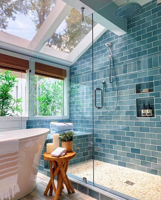 a beautiful blue attic bathroom with skylights and windows, a shower space and a bathtub plus touches of wood