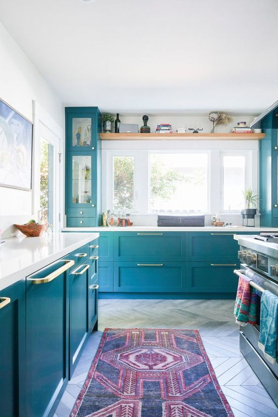 a beautiful blue kitchen with lots of natural light, touches of gold and white countertops plus a backsplash