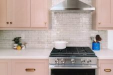a beautiful blush kitchen with brass handles, a white tile backsplash and skylights is very tender and delicate