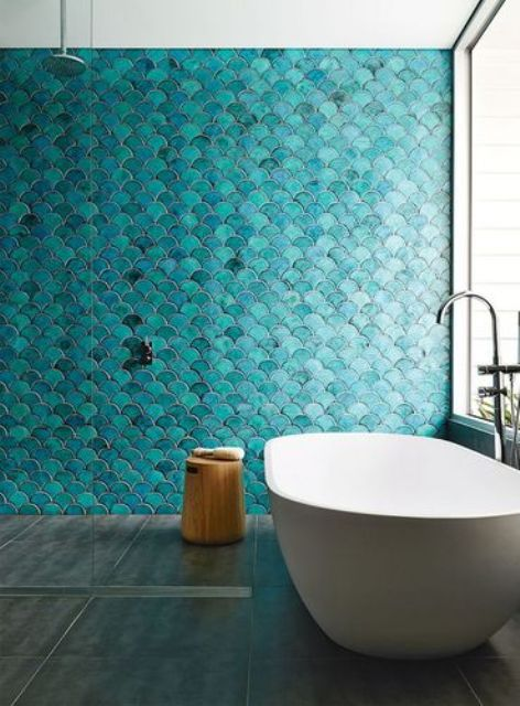 a beautiful contemporary bathroom with a turquoise fish scale tile wall, a white tub and a wooden stool is lovely