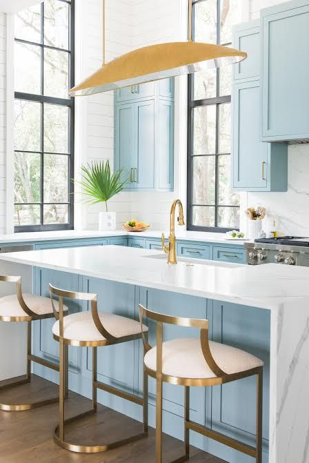 a beautiful light blue kitchen with white marble countertops and a backsplash plus touches of gold and brass