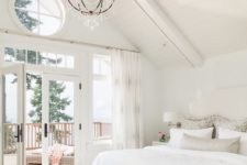 a beautiful neutral attic bedroom with a white bed, a grey bench, printed textiles and a blacony with a view