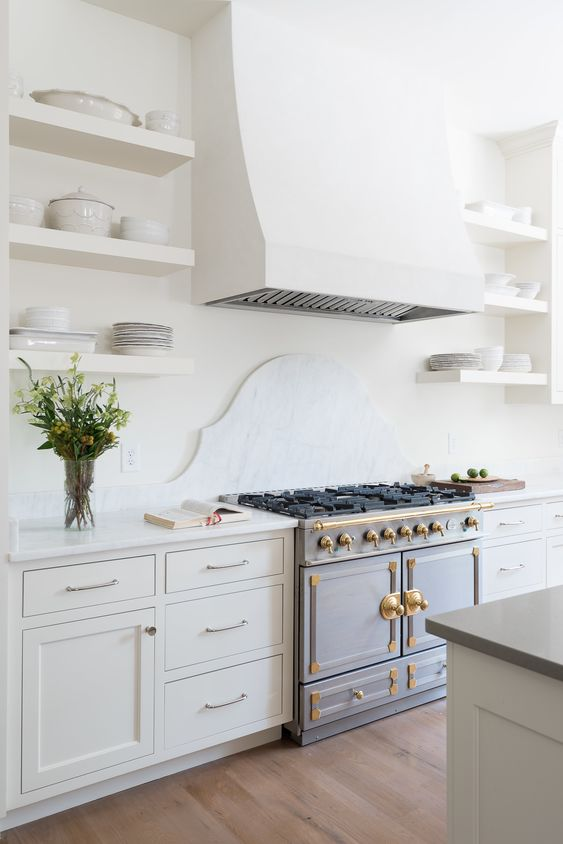 a beautiful neutral kitchen with a white marble backsplash, chic cabinets, a vintage cooker, a large hood and open shelves