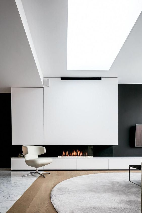 a black and white wall with a built in fireplace, a grey rug, a white chair and a skylight to light up the space