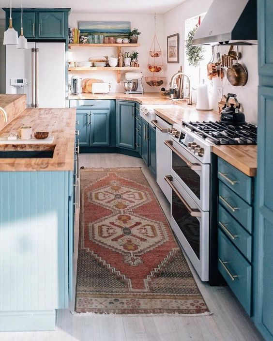 a blue farmhouse kitchen with wooden countertops, a white backsplash and pendant lamps