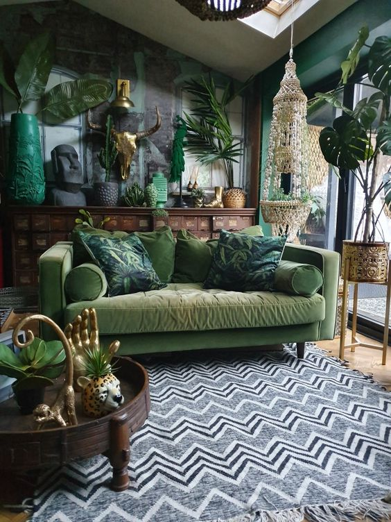 a boho living room with a black brick wall and green walls, a muted grene sofa, potted plants and boho accessories and details