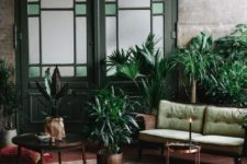 a boho living room with industrial walls, a green loveseat, vintage green doors, potted plants and boho pillows