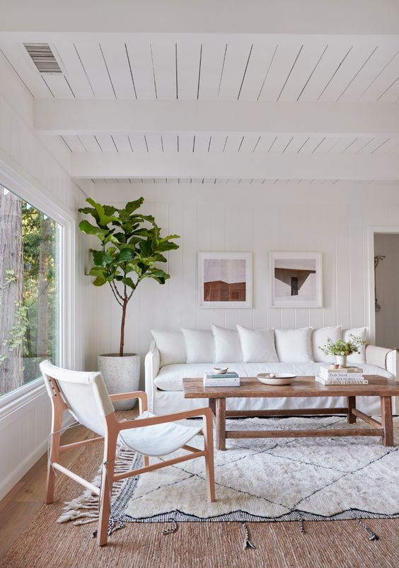 a boho living room with white furniture, a wooden coffee table, a small gallery wall and a tree