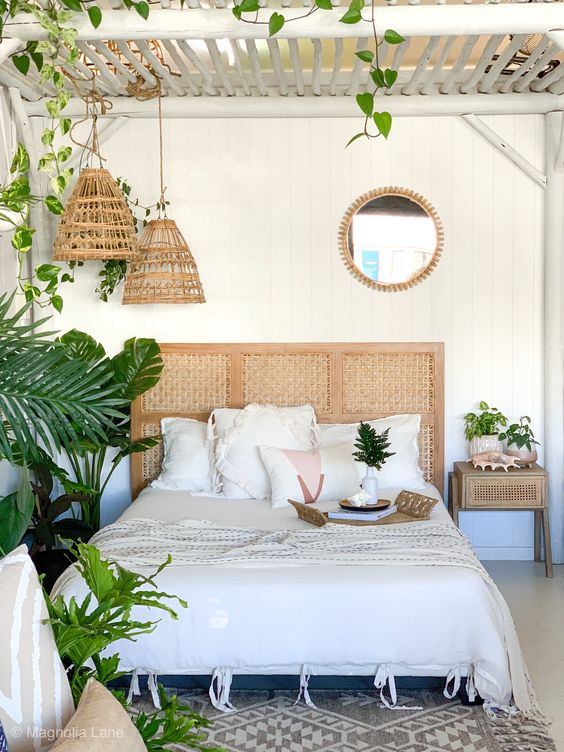 a boho tropical bedroom done in neutrals, a white wooden ceiling, woven pendant lamps and a cool rattan headboard plus lots of greenery
