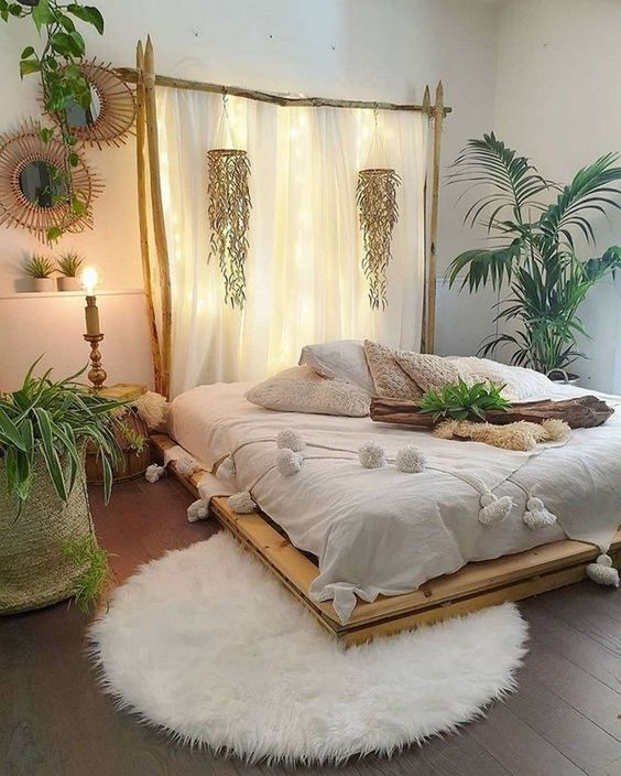 a boho tropical bedroom with a pallet bed, a lit up headboard of fabric, woven touches and tropical plants