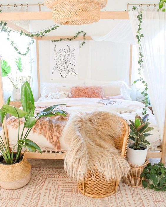 a boho tropical bedroom with a wooden bed, a peacock chair, potted plants and greenery and a woven chandelier
