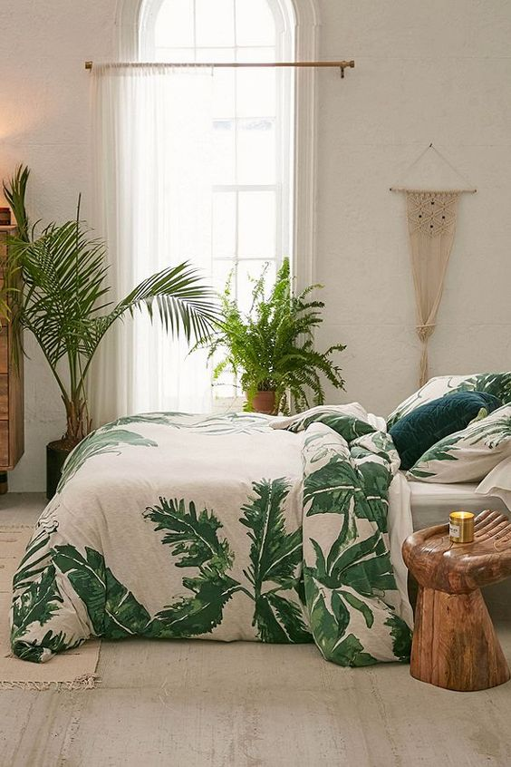a boho tropical space with a macrame hanging, tropical bedding, wooden furniture and potted plants