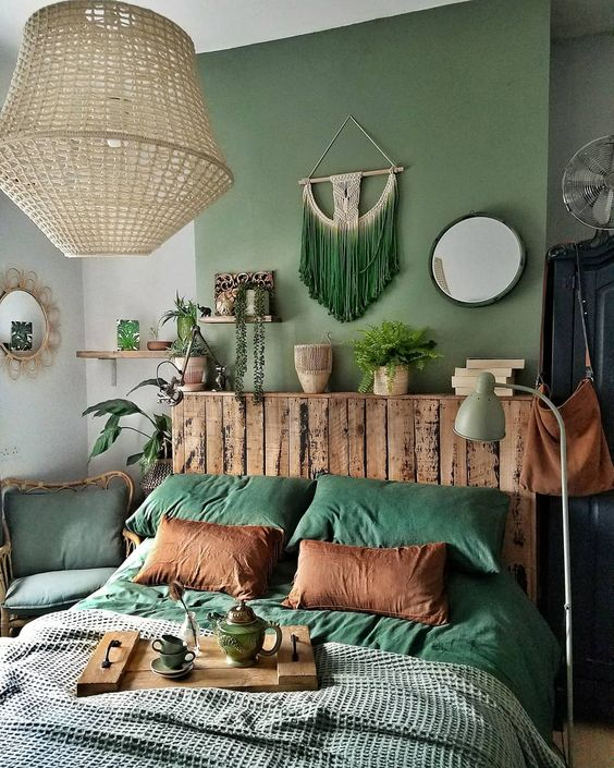 a bold and chic boho bedroom with a green accent wall, a green macrame hanging, green chair and bedding plus touches of wood looks lovely
