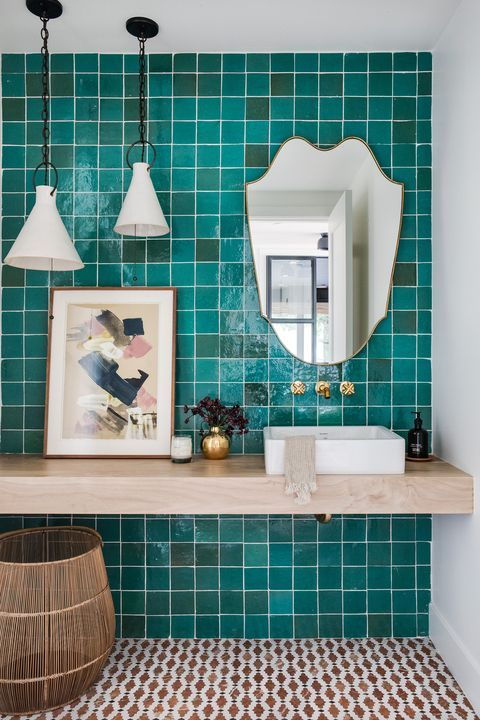 a bold bathroom with a turquoise tile wall, a floating vanity, pendant lamps and a quirky mirror is wow