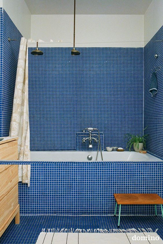 a bold blue tile bathroom with a built-in tub, a wooden vanity and a printed shower curtain