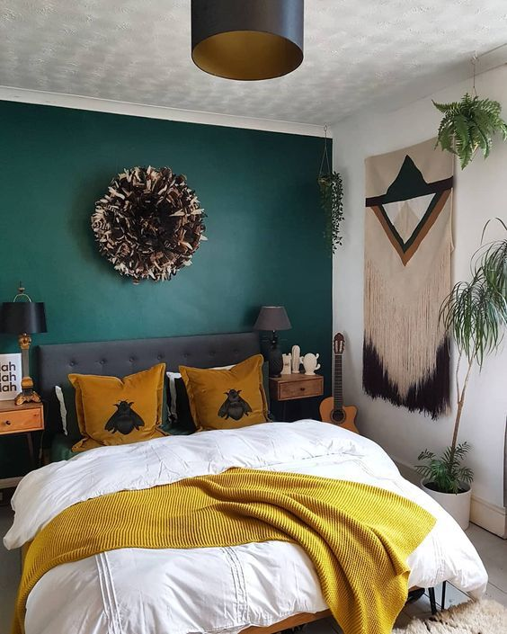 a bold boho bedroom with a hunter green accent wall, mustard touches, a macrame hanging and black details for drama