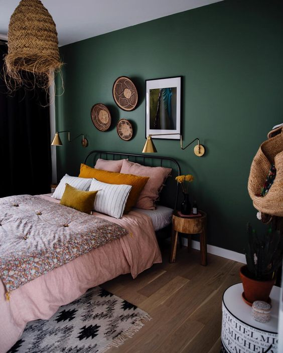 a bold boho bedroom with hunter green walls, a metal bed, a woven pendant lamp and a chic gallery wall