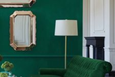a bold living room with an emerald wall, a grene velvet sofa and touches of gold and copper for more chic