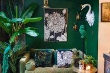 a bold living room with emerald walls, a muted grene sofa, potted plants and a parrot figurine in emerald
