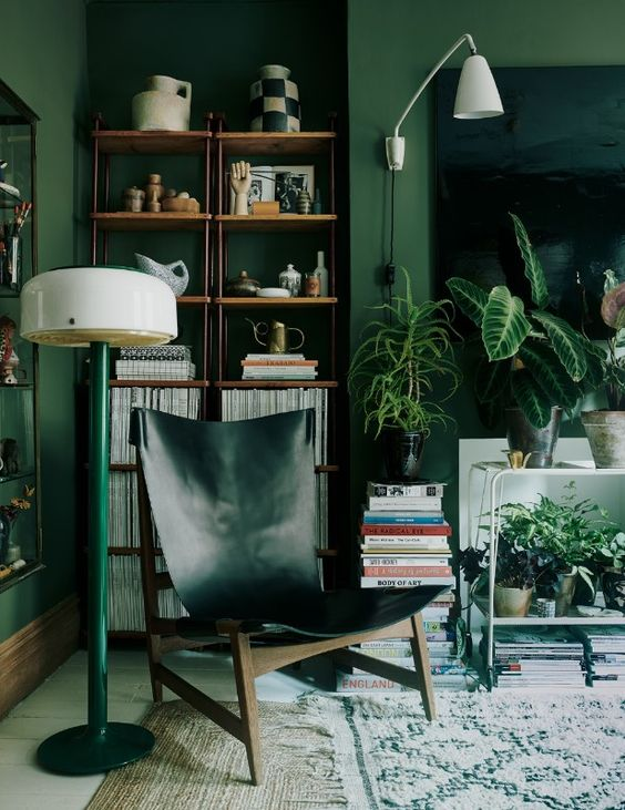 a bold living room with green walls, a hunter green leather chair, a green lamp and lots of plants feels comfy