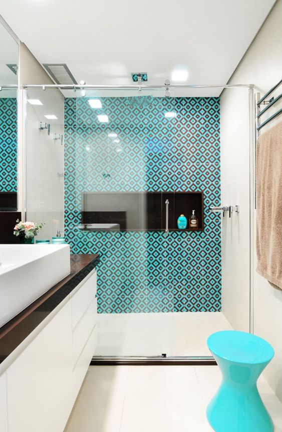 a bold modern bathroom in neutrals, with a dark tabletop, a turquoise and brown tiles and a turquoise stool