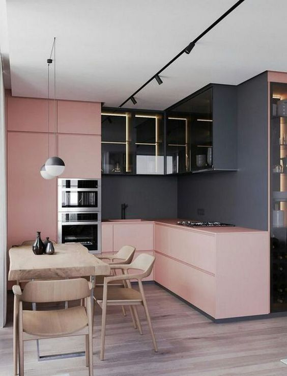 a bold modern kitchen with black walls, light pink sleek cabinets, lit up black upper cabinets