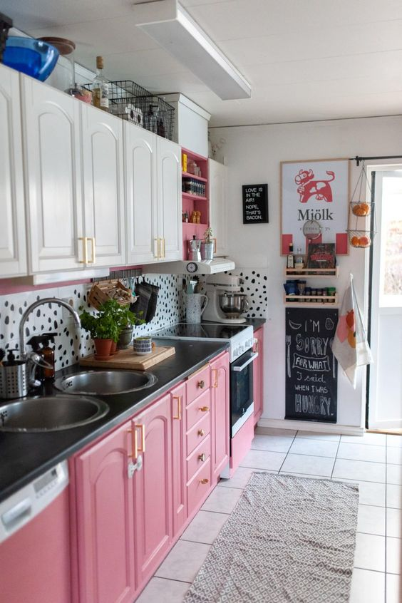 a bright and fun kitchen with white upper cabinets, hot pink lower ones and a pretty dolmatin print backsplash