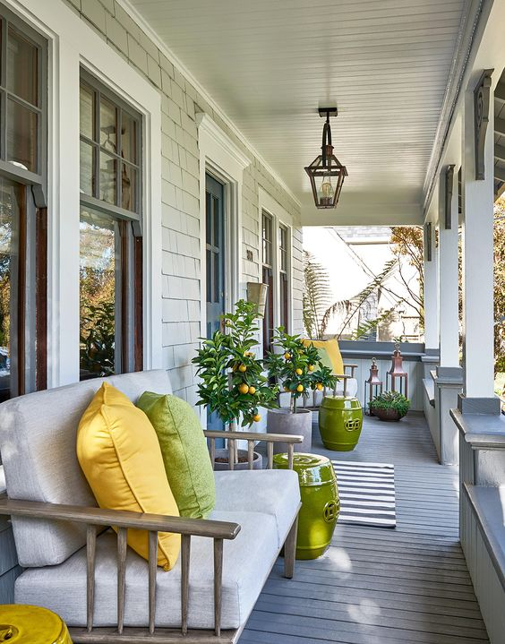 a bright and welcoming summer porch with citrus trees, a neutral loveseat with bright pillows and side tables