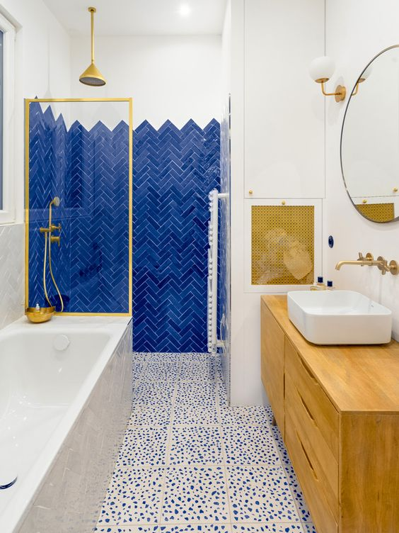 a bright bathroom with a bold blue accent tile, Dolmatin print tile, touches of gold and a wooden vanity
