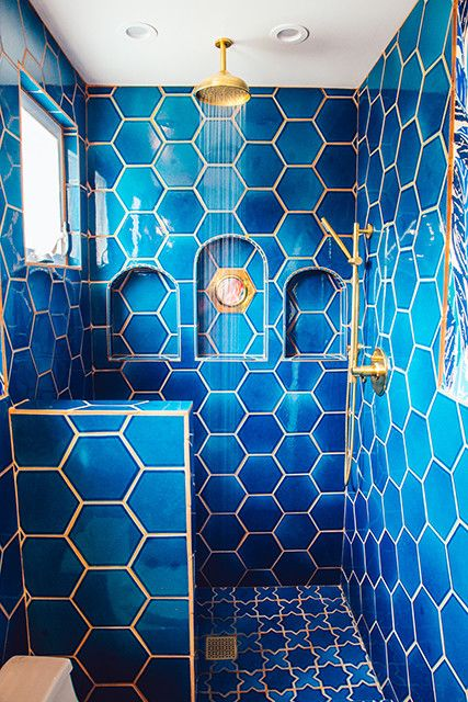 a bright blue bathroom clad with hexagon tiles and highlighted with gold touches for more chic