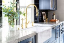a bright blue kitchen with a black tile backsplash, white stone countertops and touches of gold for more chic
