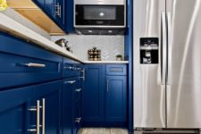 a bright blue kitchen with a white chevron tile backsplash, stainless steel appliances and simple handles