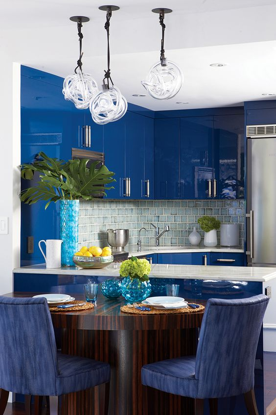 a bright blue kitchen with sleek and shiny cabinets, a neutral tile backsplash and pendant lamps plus white countertops