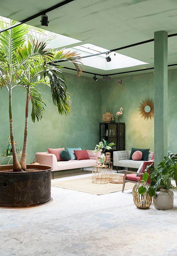 a bright living room with green plaster walls and a ceiling, with grey and pink furniture and colorful pillows and lots of potted greenery