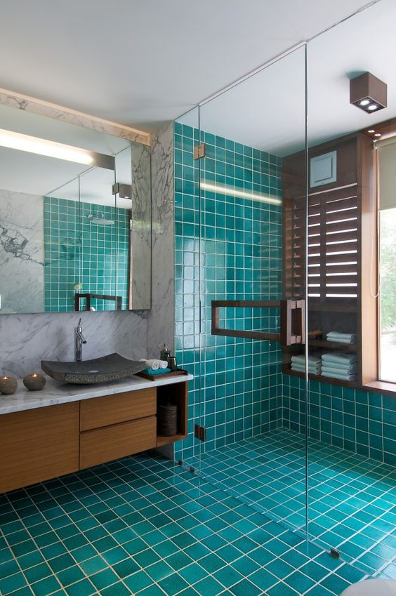 a bright modern bathroom with turquoise tiles, marble walls, a wooden vnaity, a stone sink and a statement mirror
