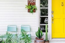 a bright modern porch with a sunny yellow door, cacti in pots and greenery and blue chairs to relax here