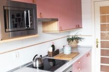 a bright pink modern kitchen with leather handles, neutral countertops and a backsplash looks chic and cool