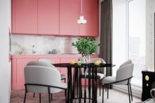 a bright pink modern kitchen with sleek cabinets, a shiny backsplash and a pendant lamp plus an elegant dining space