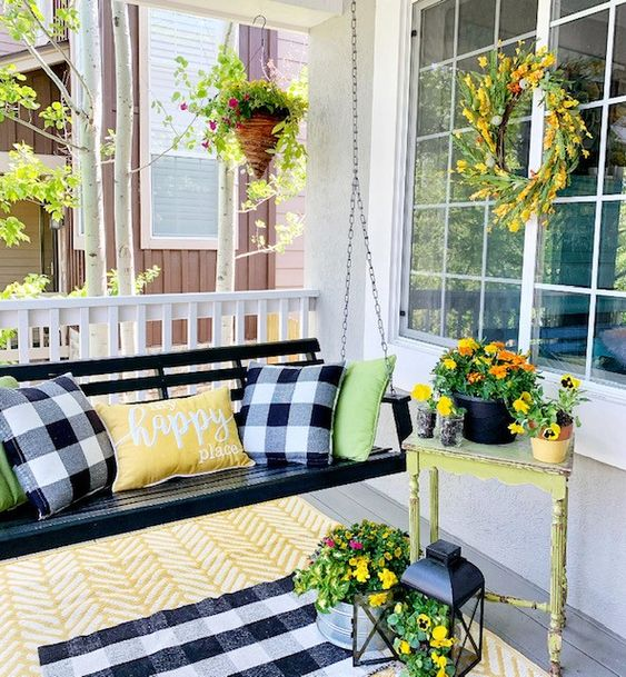 a bright summer porch with a black hanging bench, a vintage table, a candle lantern and lots of colorful blooms
