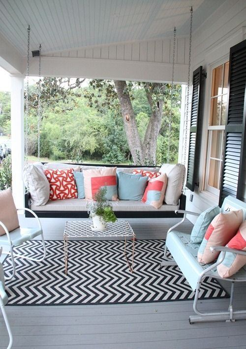 a bright summer porch with a hanging bench, white and mint furniture, colorful pillows and a printed rug
