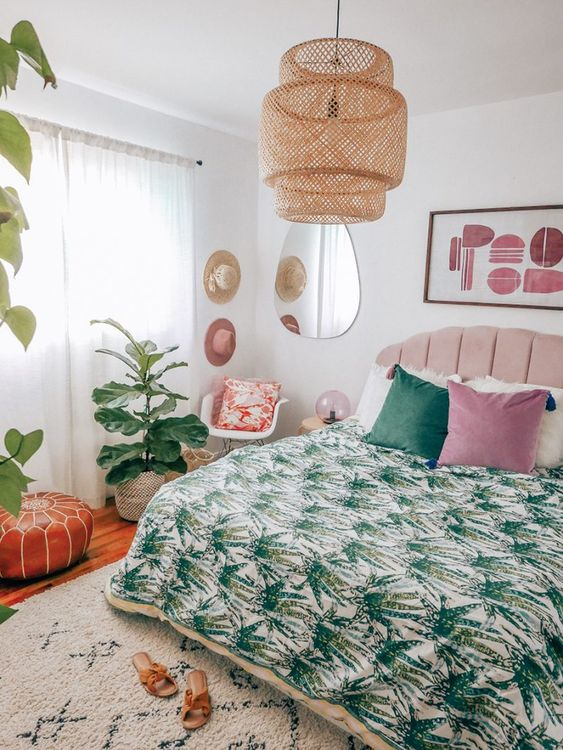 a bright tropical-infused bedroom with a pink bed, a wicker lamp, printed bedding, potted tropical plants