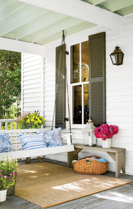 a bright vintage-inspired front porch with a hanging white bench, colorful pillows, a bench, a basket and lots of blooms