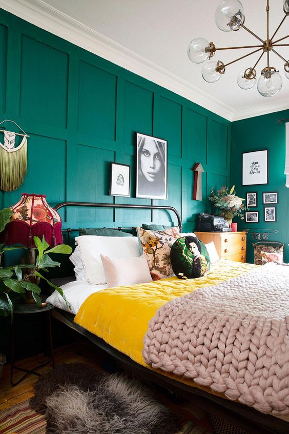 a bright bedroom with emerald green panel walls, bright and printed bedding, printed lamps and potted greenery